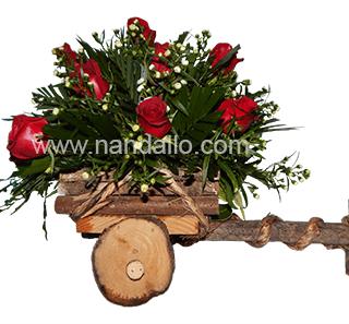 Arreglo de rosas rojas en carreta de madera