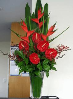Arreglo con flores tropicales y base de vidrio